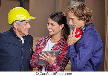 Carpenters With Digital Tablet In Workshop