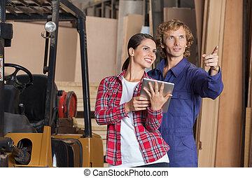 Carpenters With Digital Tablet Planning In Workshop