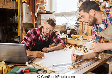 carpenters with laptop and blueprint at workshop -...