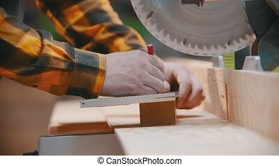 Carpentry - a man woodworker making marks for cutting on the wooden detail with a pencil and yardstick - a circular saw on the background