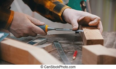 Carpentry - a woodworker cutting out the recess on the wooden block