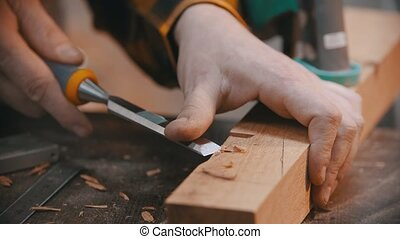 Carpentry - a woodworker cutting out the recess on the wooden block with a chisel - a man working without gloves