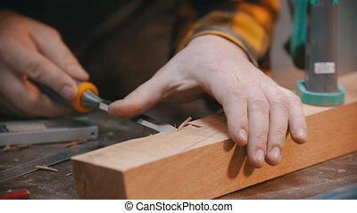 Carpentry - a woodworker cutting out the recess on the wooden block with a chisel