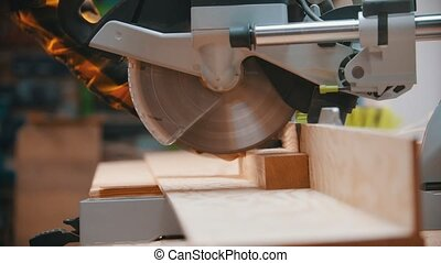 Carpentry - a woodworker cutting the wooden detail with a circular saw