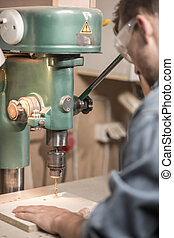 Carpentry drill operated by worker