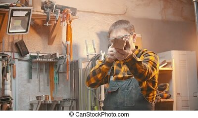Carpentry indoors - a man woodworker inspect cuted detail for the bumps and imperfections. Mid shot
