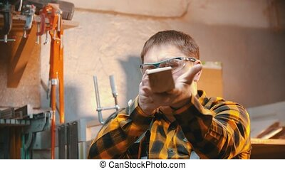 Carpentry indoors - a man woodworker inspect cuted detail for the imperfections. Mid shot