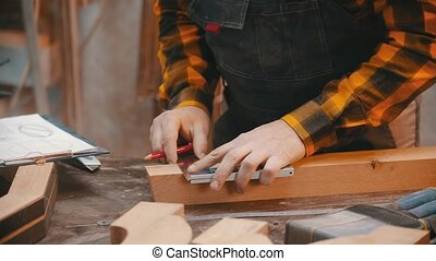 Carpentry indoors - a man woodworker making marks for cutting on the wooden detail with a pencil and yardstick