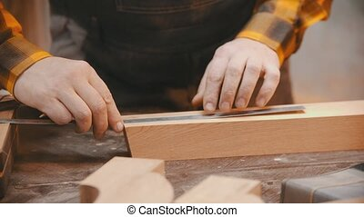 Carpentry indoors - a man woodworker making marks on the wooden detail with a pencil and yardstick