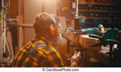 Carpentry indoors - a man woodworker measuring the thickness...