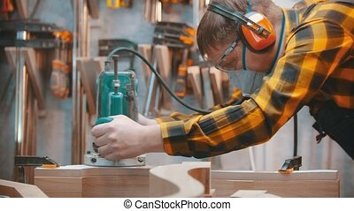 Carpentry indoors - a man woodworker polishes a wooden plank...