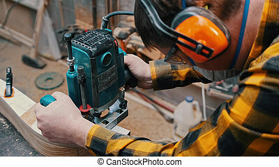 Carpentry indoors - a woodworker polishes the wooden detail from the top in the workshop- a man using protective headphones