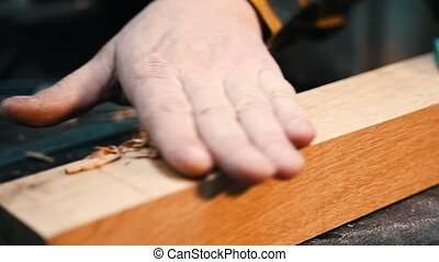 Carpentry industry - a man woodworker cutting out the recess on the wooden detail with a chisel