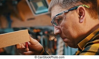 Carpentry industry - a man woodworker inspect cuted detail for the imperfections. Mid shot
