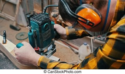 Carpentry industry - a man woodworker polishes the top of ...