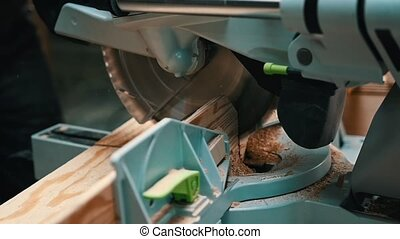 Carpentry industry - a woodworker cutting a piece of wood ...