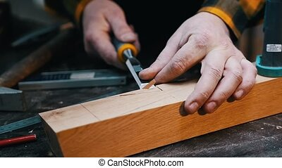 Carpentry industry - a woodworker cutting out the recess on the wooden block with a chisel