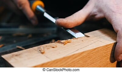 Carpentry industry - a woodworker cutting out the recess on the wooden detail with a chisel and his hands