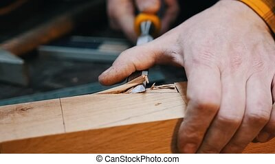 Carpentry industry - a woodworker cutting out the recess on the wooden detail with a chisel