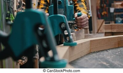 Carpentry industry - a woodworker polishes the side of the wooden detail in a workshop