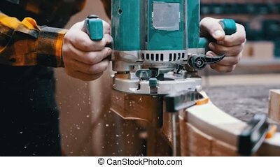 Carpentry industry - a woodworker polishes the side of the wooden detail