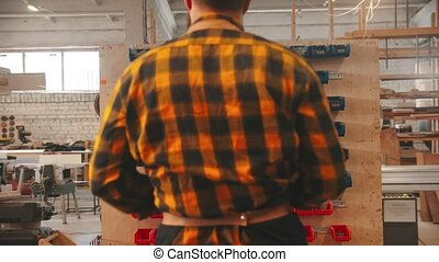 Carpentry industry - handsome man worker walking to the stand with different screws