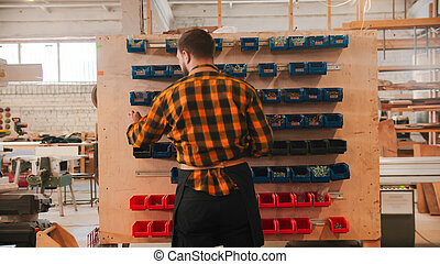 Carpentry industry - man choosing screws from the stand