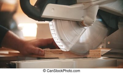 Carpentry industry - man cutting out the piece of wood using big circular saw