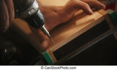 Carpentry industry - man worker drills screws into the piece of plywood in the workshop