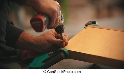 Carpentry industry - man worker drills screws into the piece of plywood