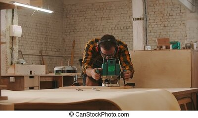 Carpentry industry - man worker in protective glasses and headphones cutting a wooden item