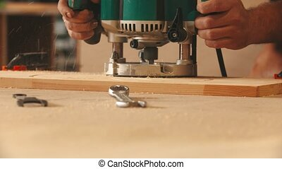 Carpentry industry - man worker in protective glasses and headphones cutting out the patterns out of the wooden plank