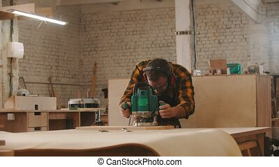 Carpentry industry - man worker in protective glasses and headphones grinding a wooden item in the workshop