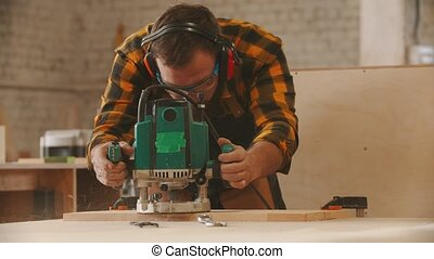 Carpentry industry - man worker in protective glasses and headphones grinding a wooden item