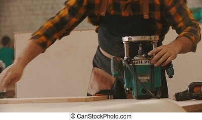 Carpentry industry - man worker sets up the grinding machine