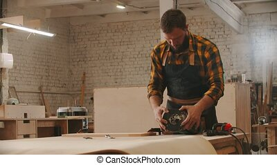 Carpentry industry - man worker sets up the grinding machine on the table
