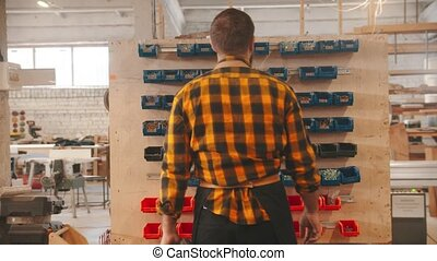 Carpentry industry - man worker walking to the stand with different screws