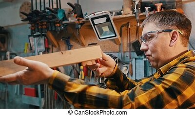Carpentry industry - working in the workshop - a man woodworker in protective glasses inspect wooden detail for the imperfections. Mid shot