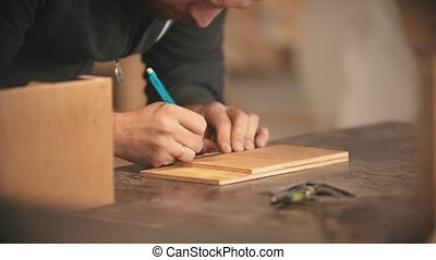 Carpentry working - bearded man making marks on the wood