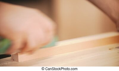 Carpentry working - hands of man worker polishing the wooden plank