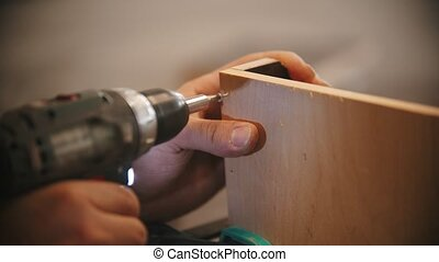 Carpentry working - man worker drills screws into the ...