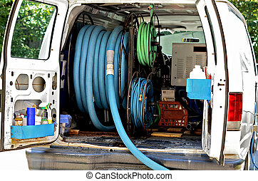 A van with equipment in the back for cleaning carpet.