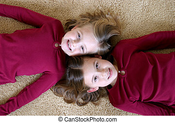 Carpet Critters - smiling young girls in red shirts laying...