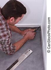 Carpet fitter laying pvc flooring