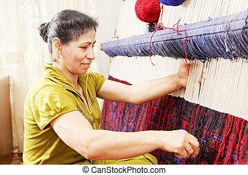 Carpet weaver sideview closeup - Carpet weaver at work in ...