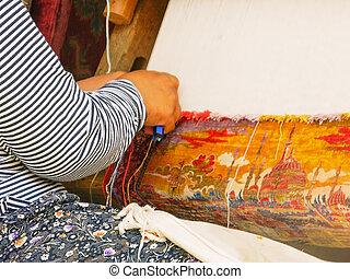 Turkish women are engaged in carpet weaving