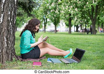 carrera mezclada, estudiante universitario, el sentarse en la hierba, trabajando