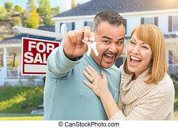 carrera mezclada, pareja, con, llaves, delante de, signo bienes raíces, y, casa nueva