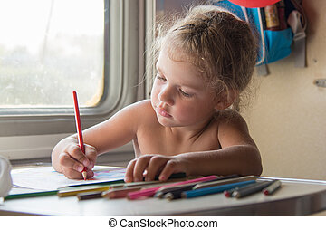 Carried away by the girl draws pencils at the table in a train