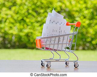 carro de compras, con, receiptwith, coins, en, tabla de madera, concepto, para, tienda de comestibles, gastos, y, consumismo